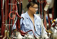 A worker looks up while assembling automobiles at the Shanghai Volkswagen (SVW) plant in Shanghai, China..