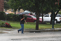 NWA Democrat-Gazette/J.T.WAMPLER A pedestrian crosses Dickson Street in Fayetteville Sunday Oct. 6, 2019 during a rainstorm. Rain is likely today (MONDAY OCT 7) along went a cold front that will bring low temperatures in the 40s and 50s this week.
