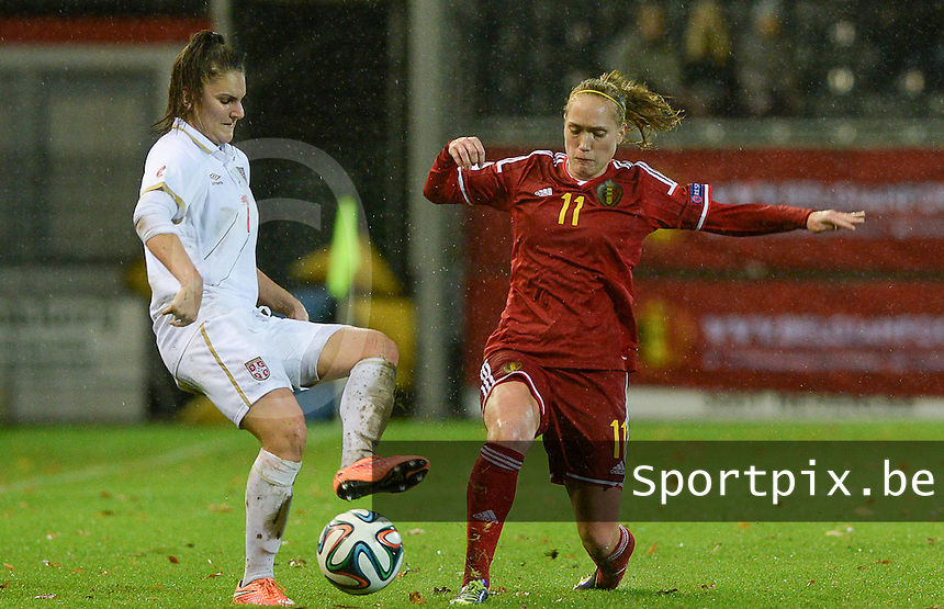 20151130 - LEUVEN ,  BELGIUM : Belgian Janice Cayman (r) pictured in a duel with Serbian Jovana Damnjanovic (left) during the female soccer game between the Belgian Red Flames and Serbia , the third game in the qualification for the European Championship in The Netherlands 2017  , Monday 30 November 2015 at Stadion Den Dreef  in Leuven , Belgium. PHOTO DAVID CATRY