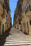 Steps climb hill of narrow street historic housing with traditional balconies in city centre of Valletta, Malta