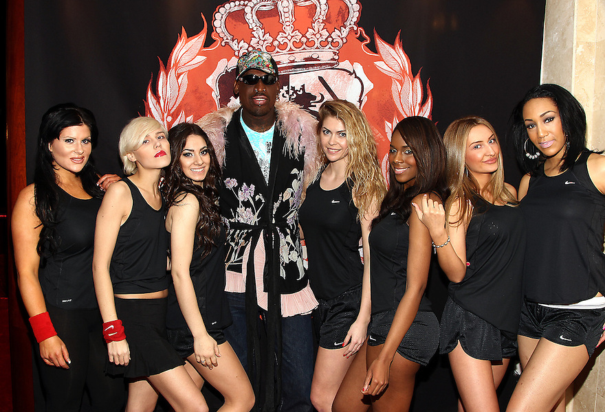 Players Adrienne, Polina, Candice, coach Dennis Rodman, Kristina, Tanisha, Inga and Layla pose for a photo at the press conference for HQ's strippers basketball team in New York, on Thursday, Mar. 01, 2012. (AP Photo/ Donald Traill)