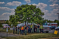 Westerville, Genoa and Ohio State university police officers and the Westerville Fire Department stand in the shade of a tree in the parking lot after training at a high school to refine their procedures and policies for school violence..