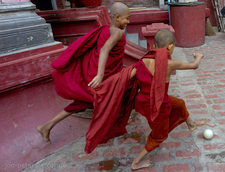 young monks playing soccer during leisure time in monastery clos