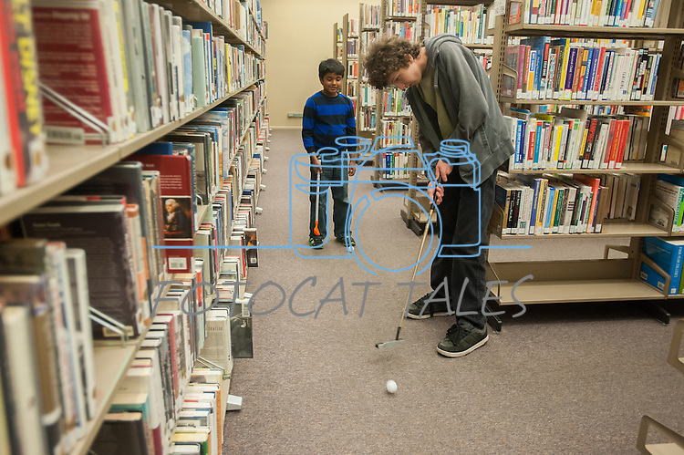 Ryan Fitzsimmons attempts a putt while being watched by fellow golfer Sohan Vadlakunta during the Mini Golf Night at the Carson City Library on Friday May 9, 2014. Kids and parents built a custom mini golf course throughout the library using anything at their disposal and engineering ideas to make a difficult course. Everything from tables to shelves were used to create creative courses.<br />