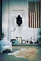 An informal living room with painted brick work. An armchair with a textured cover is placed in front of a selection of items displayed on a low step. An animal head and a Stars and Stripes flag are displayed on the wall above.