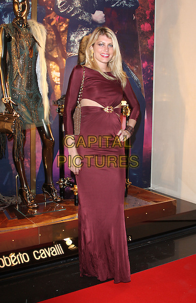 Meredith Ostrum.Roberto Cavalli Store Launch Party during London Fashion Week, Sloane Street, London, England, UK, .September 17th 2011..LFW full length cut out long maxi dress hand on hip gold burgundy cuff bag  red .CAP/ROS.©Steve Ross/Capital Pictures