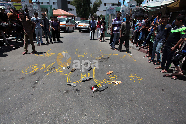 "Palestinians walk next to a write on the ground that reads ""Abbas is a traitor"" during a protest against the Palestinian President Mahmoud Abbas and the unity government ministers, outside al-Shifa hospital in Gaza City on July 15, 2014. Palestinian President Mahmoud Abbas, who reached an agreement with Hamas in April that led to the formation of a unity government last month, welcomed the Egyptian-proposed deal that would halt the week-old Gaza shelling war, as did the Arab League, which called on ''all parties'' to accept the truce, but the Palestinian territories dominant Hamas Islamists responded suspiciously, saying they had not been consulted by Cairo. Israel said there had been two cross-border launches overnight that caused no damage, and that it had bombed 25 sites in Gaza. Photo by Ashraf Amra"