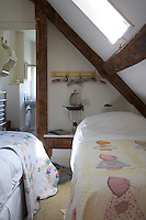 Twin beds are tucked under the eaves in this child's attic bedroom where there is just enough room for an en-suite bathroom