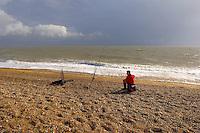 boy fishing off the shingle beach at Aldeborough, Suffolk, England