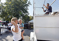 NWA Democrat-Gazette/FLIP PUTTHOFF<br />PITCH FOR CENTERTON DAY<br />Tina Polk of Bentonville and her granddaughter, Kori Cale, 2, wind up for a throw Saturday Sept. 9 2017 to dunk Nicholas Bower, a teacher and girl's basketball coach at Bentonville West High School, at the dunk during the annual Centerton Day. The annual event included a parade, tiny tot pageant, car show and more held at Centerton city park and other venues around the city.