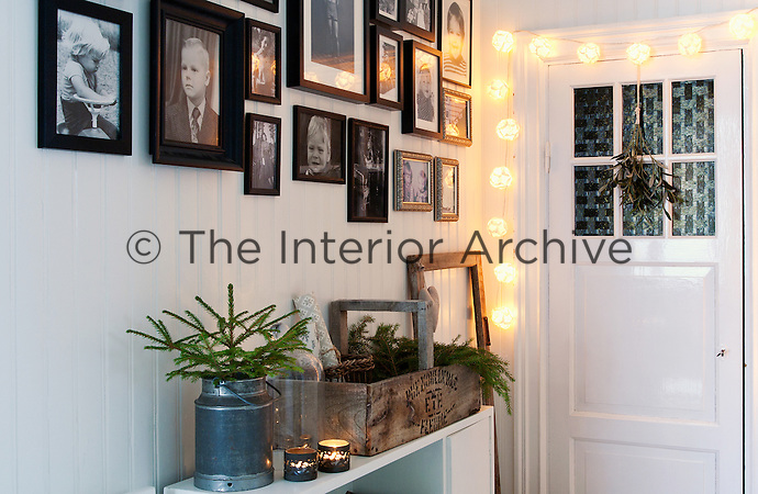 In the top floor corridor, a collage of black and white photographs is displayed on the tongue and groove wall