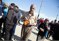 Pictured: An eldrerly man with oranges he was given as a handout Thursday 03 March 2016<br /> Re: Migrants have closed off the railway track at the Greek Fyro Macedonian border in Idomeni, Greece,