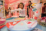 Young visitors play a Hello Kitty roulette game at the opening of Hello Kitty's Kawaii (Cute) Paradise, a Hello Kitty theme store, in Tokyo, Japan on Thursday 21 October  2010. .Photographer: Robert Gilhooly