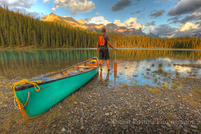 Man standing with his canoe on the shores of Maligne Lake, Jasper National Park.