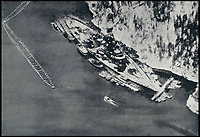 BNPS.co.uk (01202 558833)<br /> Pic:  BNPS<br /> <br /> The heavily defeded Tirpitz sheltering in a Norweigan fjord.<br /> <br /> The gallantry medals awarded to one of the heroes of a daring raid on the Tirpitz who later escaped a Nazi death march have emerged for sale for &pound;50,000.<br /> <br /> Engine Room Artificer 4th Class Edmund Goddard was the helmsman of the midget submarine X6 which attacked the heavily protected battleship while it was docked in the Norwegian fjords.<br /> <br /> They sneaked under the giant 820ft vessel and set off four depth charges, with the force of the explosion putting the 43,000 tonne Tirpitz 7ft out of action for six months.<br /> <br /> Goddard, one of just six survivors from the raid, was captured and sent to a POW camp in Germany. He was later awarded the prestigious Conspicuous Gallantry Medal.