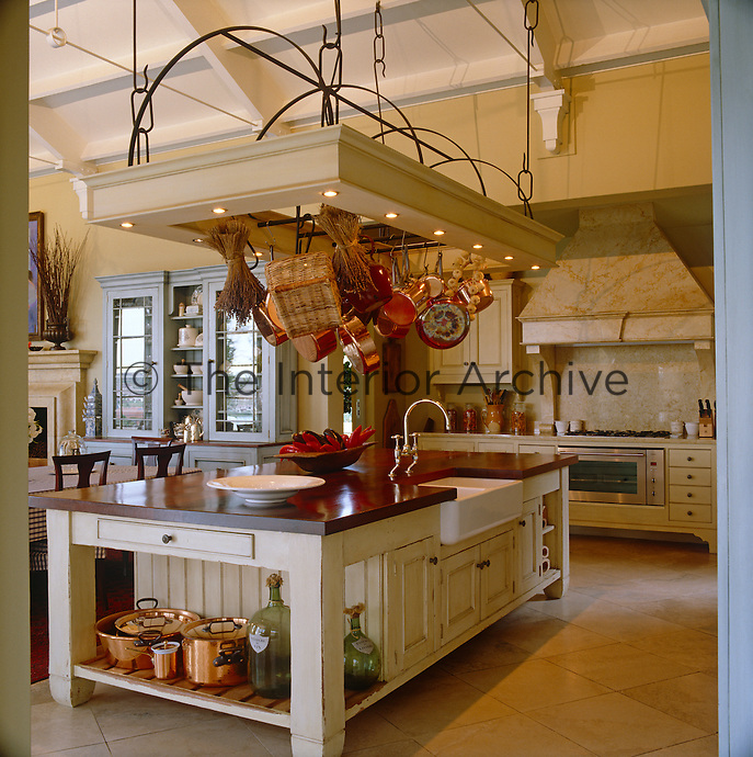 In the open plan living-area of this country  house  copper pots glow on the shelves and from a ceiling rack in the baronial-style kitchen