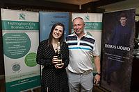 Denada Berisha of Remus Uomo gives a raffle prize to Mark Deakin