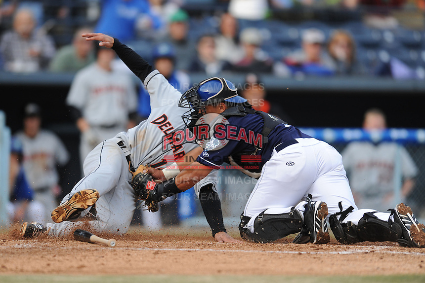 Asheville Tourists catcher Wilfredo Rodriguez #3 fields a throw and puts the tag on Anthony Caronia #14 during a game against the Delmarva Shorebirds at McCormick Field on April 5, 2014 in Asheville, North Carolina. The Tourists defeated the Shorebirds 5-3. (Tony Farlow/Four Seam Images)