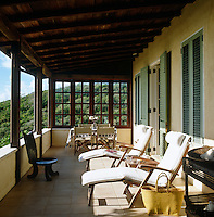 A pair of sunloungers drenched in sunlight on one of several balconies that surround the property