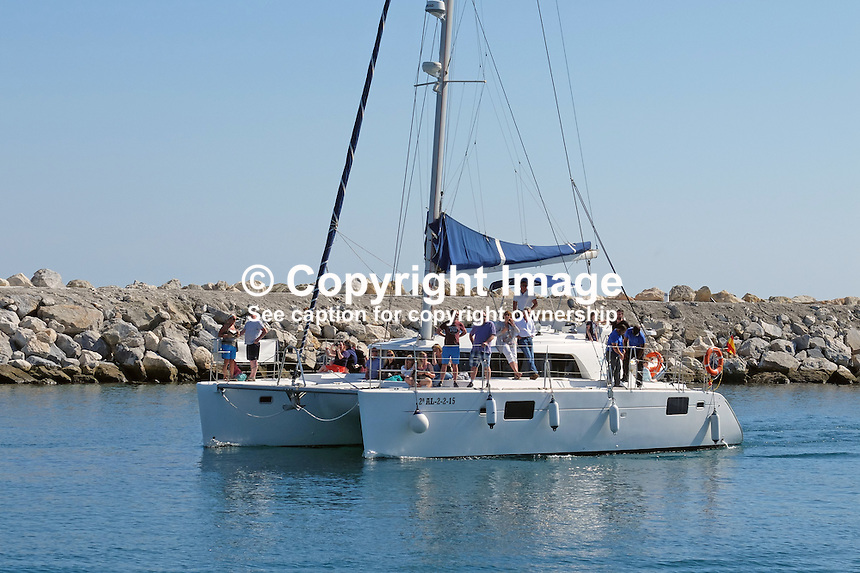 Catamaran enters harbour, Puerto Banus. Yachts, marina, harbour, Puerto Banus, Marbella, Spain, April, 2016, 201604142408<br /> <br /> Copyright Image from Victor Patterson, 54 Dorchester Park, Belfast, UK, BT9 6RJ<br /> <br /> t1: +44 28 9066 1296 (from Rep of Ireland 048 9066 1296)<br /> t2: +44 28 9002 2446 (from Rep of Ireland 048 9002 2446)<br /> m: +44 7802 353836<br /> <br /> e1: victorpatterson@me.com<br /> e2: victorpatterson@gmail.com<br /> <br /> The use of my copyright images is subject to my Terms & Conditions.<br /> <br /> It is IMPORTANT that you familiarise yourself with them. They are available on my website at www.victorpatterson.com.<br /> <br /> None of my copyright images may be used on a website unless they are visibly watermarked, i.e. © Victor Patterson within the body of the visible image. Metadata denoting my copyright must NOT be deleted. <br /> <br /> Web use is extra at currently recommended NUJ rates.