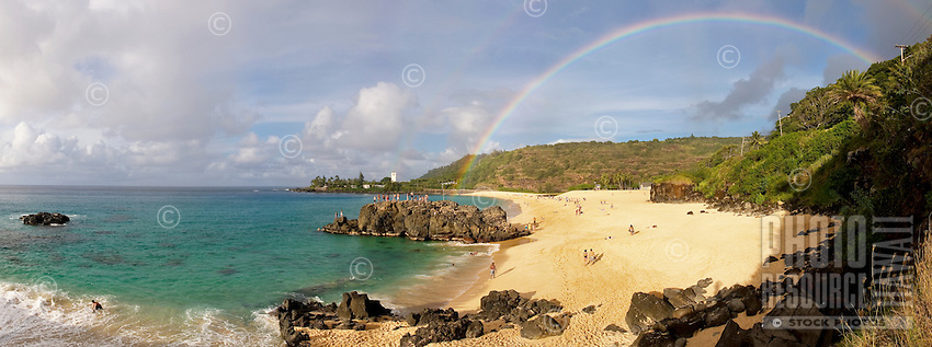 Double rainbow at Waimea bay. Wide angle panoramic shot. Jumping rock in the middle of the shot.