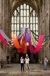 Pictured: Visitors admire the vibrant colours of the art installation 'Held in a Burst of Colour' by Rev'd Gill Sakakini as it drapes across the empty nave at Winchester Cathedral, Hants.<br /> <br /> The bright, bold colours of the fabric pay tribute to the rainbows that people across the country have been placing in their windows during the coronavirus pandemic as a symbol of hope, and welcomes visitors as they enter the Cathedral as it reopened for public service last weekend. <br /> <br /> © Jordan Pettitt/Solent News & Photo Agency<br /> UK +44 (0) 2380 458800