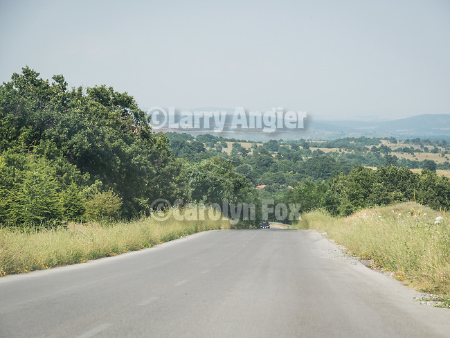 Driving the rural roadway in the green rolling hills near Mladinovo, Bulgaria
