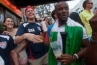 Kansas City, MO - Monday, June 16, 2014:  USA soccer fan Anthony Walker of Kansas City shares a laugh with Nigeria soccer fan Kelvin Igumbo while watching the USA vs. Ghana first round World Cup match at a public viewing in the Power and Light District of Kansas City, Missouri.