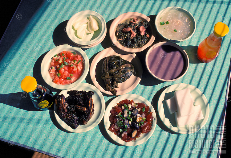 Hawaiian food plates (luau squid, long rice, lomi salmon, lau lau, poi, soy sauce, poke, haupia,) from Helena's restaurant, Honolulu, Oahu