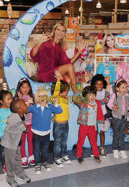Heidi Klum.debut of her Truly Scrumptious Collection at Babies R Us in Calabasas, California, USA..14th September 2012.full length pink dress hands arms waving kids children sheer sitting legs crossed .CAP/ROT/TM.© TM/Roth/Capital Pictures