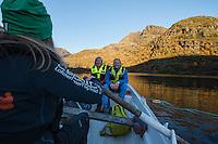 Hikers use rowboat on lake Trolldalsvatnet to access distant mountain peak, Moskenesøy, Lofoten Islands, Norway
