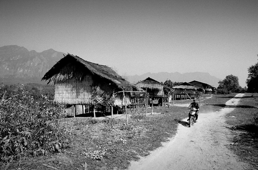 "Mekong Dam Victims - Laos. One of the 'new' relocated villages, situated far away from the original setting by the riverside, that will be flooded and has to be moved for the second time when the Theun Hinboun Expansion Project (THXP) will be completed. Numerous villages have been obligated to relocate up in the hills because of dangerous erosion and unpredictable floodings in the river. After the construction of the Theun-Hinboun Dam in Laos more than 29,000 people in 71 villages have lost fisheries, rice fields, vegetables gardens and fresh drinking water supplies as a result of the dam. An expansion project is currently under construction and will displace another 4,200 mostly indigenous people from their lands in the reservoir area and displace or negatively affect another 50,000 people living downstream, on project construction lands, and in resettlement host villages. Known as ""The Mother of Waters"", more than 60 million people depend on the Mekong river and its tributaries for food, fresh water, transport and other aspects of daily life. The construction of big dams is now threatening the life of these people aswell as the vital and unique ecosystem of the river."