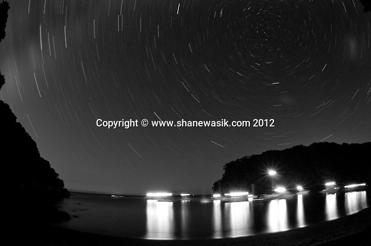 Lights from the anchored launches reflect across south east bay at Tuhua / Mayor Island, as the stars track across the sky.