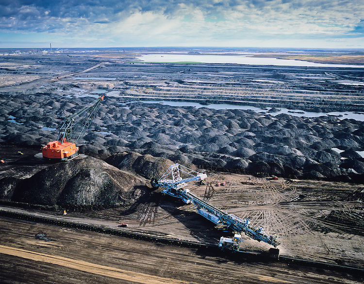 Syncrude Operations..Alberta Oil Sands. Northern Alberta.. These oil reserves are second only to those of Saudi Arabia. Their method of extraction is among the most damaging and their refining creates more greenhouse gases than any other oil refining process..Copyright Garth Lenz. Contact:  lenz@islandnet.com www.garthlenz.com ..Copyright Garth Lenz. Contact: lenz@islandnet.com www.garthlenz.com