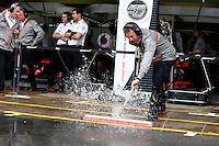 SAO PAULO, SP, 23.11.2013 - F1 - TREINOS LIVRES -  Mecanido da McLaren empurra agua para fora dos boxes, durante o treino livre deste sábado (23) para o Grande Prêmio do Brasil de Fórmula 1, no autódromo de Interlagos, na zona sul de São Paulo. O treino de classificação para a corrida, que ocorre amanhã, começa hoje a partir das 14h. (Foto: Lukas Gorys / Brazil Photo Press).