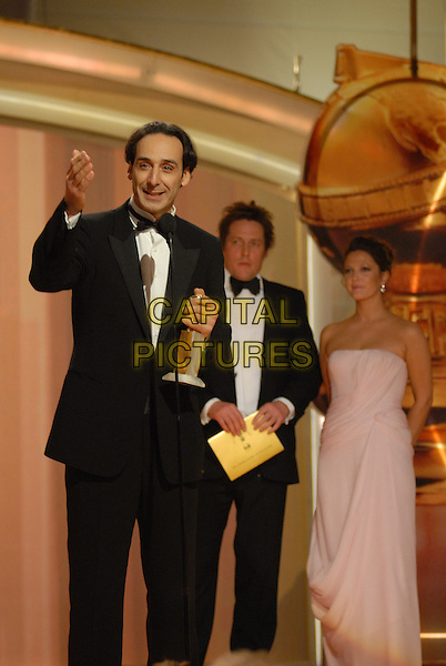 """ALEXANDRE DESPLAT, DREW BARRYMORE & HUGH GRANT.Accepts the award for Best Original Score - Motion Picture.Telecast - 64th Annual Golden Globe Awards, Beverly Hills HIlton, Beverly Hills, California, USA..January 15th 2007. .globes stage microphone half length pink strapless tuxedo black trophy.CAP/AW.Please use accompanying story.Supplied by Capital Pictures.© HFPA"""" and """"64th Golden Globe Awards"""""""