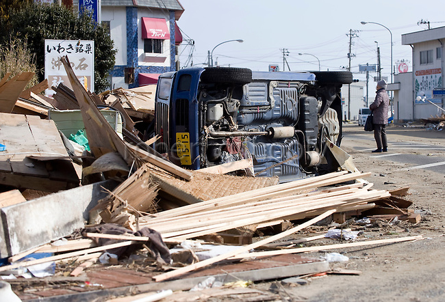 An elderly woman looks at the damage caused by the March 11 magnitude 8.8 quake in Iwaki City, Fukushima, Japan on 13 March, 2011. Some 1,500 people are reported dead and tens of thousands missing after the mega-temblor. Photographer: Robert Gilhooly