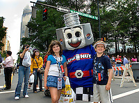 Two fans (no model releases) appear with mascot LugNut. For several days leading up to the May races at the Lowe's Motor Speedway, uptown Charlotte streets are transformed into a showcase of motor sports and non-stop entertainment. ..Photo taken in 2007. Photographer also has images from 2008.