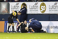 The Asssistant Referee (centre) receives treatment and cannot continue during the Sky Bet League 2 match between Luton Town and Wycombe Wanderers at Kenilworth Road, Luton, England on 26 December 2015. Photo by David Horn.