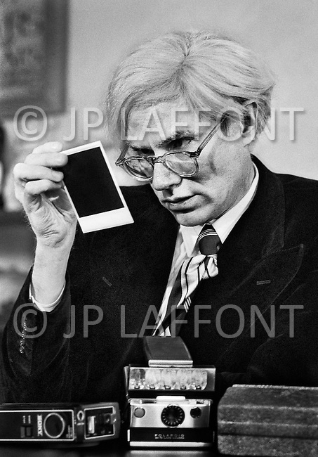 March 1st, 1974, New York City. Andy Warhol in his office on Union Square. With a true passion for photography, the artist was immediately taken by the Polaroid innovation of instantenous camera. First the instantaneous nature of the result - you no longer need to have a roll developed and wait for 1 or 2 days to see the photos. Then the immediate gratification of being able to show and share his pictures with his entourage<br /> <br />  Le 1er mars 1974, New York City<br /> <br /> Andy Warhol dans son bureau d'Union Square.<br /> L'artiste passionn&eacute; de photographie a tout de suite &eacute;t&eacute; s&eacute;duit par l'arriv&eacute; du Polaroid.<br /> <br /> D'abord l'instantan&eacute;it&eacute; du r&eacute;sultat, on ne doit plus aller faire d&eacute;velopper son film et attendre 1 ou 2 jours pour voir les photos.<br /> Enfin le plaisir imm&eacute;diat de partager et de montrer ses photos autour de lui.