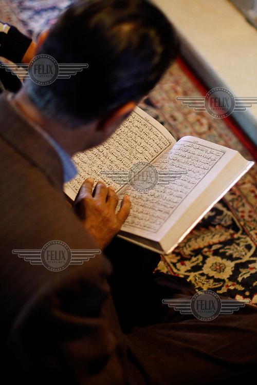 Worshipper at Makhdoom Sahib Shrine reading the koran. Srinagar, Kashmir,India. © Fredrik Naumann/Felix Features