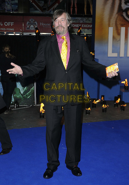 Stephen Fry.'The Life Of Pi' UK film premiere, Empire cinema, Leicester Square, London, England.3rd December 2012.full length black jacket yellow tie pink shirt stripe goatee facial hair hands arms  .CAP/CAN.©Can Nguyen/Capital Pictures.