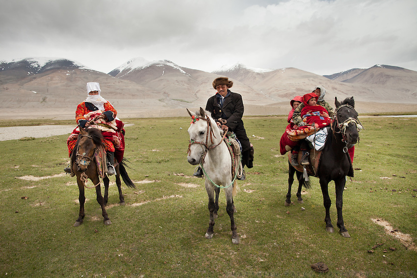 The Khan family on horse back. Nomads by necessity, the Kyrgyz move seasonally across Afghanistan's Pamir, a high altitude plateau stuck between China, Tajikistan and Pakistan, where the world's highest mountain ranges converge..Today, the Khan's family is leaving for their summer camp. Everything they own needs to be tied to the back of yaks, including a dozen teapots, a cast-iron stove, a car battery, two solar panels, a yurt, and 43 blankets...Moving with the Khan (chief) family from the Qyzyl Qorum camp to the summer camp of Kara Jylga, on the south side of the wide Little Pamir plateau...Trekking through the high altitude plateau of the Little Pamir mountains (average 4200 meters) , where the Afghan Kyrgyz community live all year, on the borders of China, Tajikistan and Pakistan.