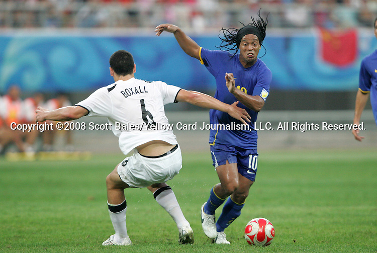10 August 2008: Ronaldinho (BRA) (10) moves past Michael Boxall (NZL) (6).  The men's Olympic soccer team of Brazil defeated the men's Olympic soccer team of New Zealand 5-0 at Shenyang Olympic Sports Center Wulihe Stadium in Shenyang, China in a Group C round-robin match in the Men's Olympic Football competition.