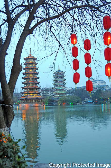 Sun and Moon towers and their reflections in the lake in Guilin, China.  Red lanterns decorate a shoreline tree for lunar New Year