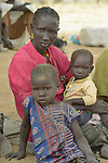 A mother and her children, internally displaced by conflict and climate, wait alongside a road in Malek Miir, a village in South Sudan's Lol State. They and thousands of other families in the region have tried to reach Sudan, but have been prevented from crossing the border. Many wait in limbo, unwilling to return to drought-stricken farms.