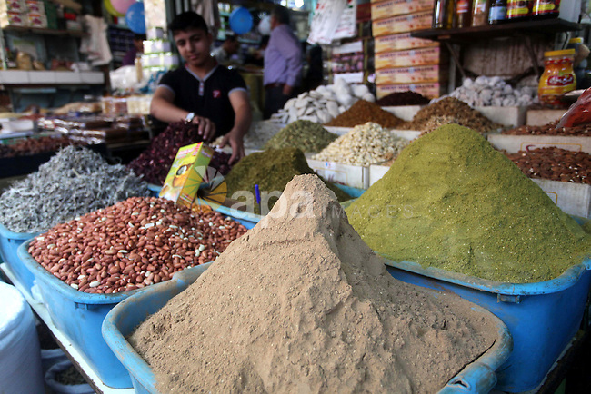 A Palestinian vendor sells spices at a market in Gaza City as the faithful prepare for the start of the Muslim holy fasting month of Ramadan on June 17, 2015. More than 1.5 billion Muslims around the world will mark the month, during which believers abstain from eating, drinking, smoking and having sex from dawn until sunset. Photo by Ashraf Amra