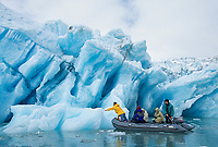 Tourists view large glacier iceberg, calved off of Nellie Juan glacier, floating in Nellie Juan Lagoon, Prince William Sound, Alaska