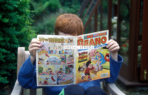 9 year old boy reading The Beano comic UK. MR