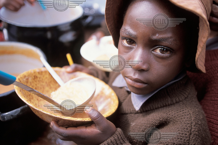A child receiving a free school lunch, provided by a UNICEF food aid scheme. Zimbabwe has suffered terrible food shortages due to drought and political turmoil.